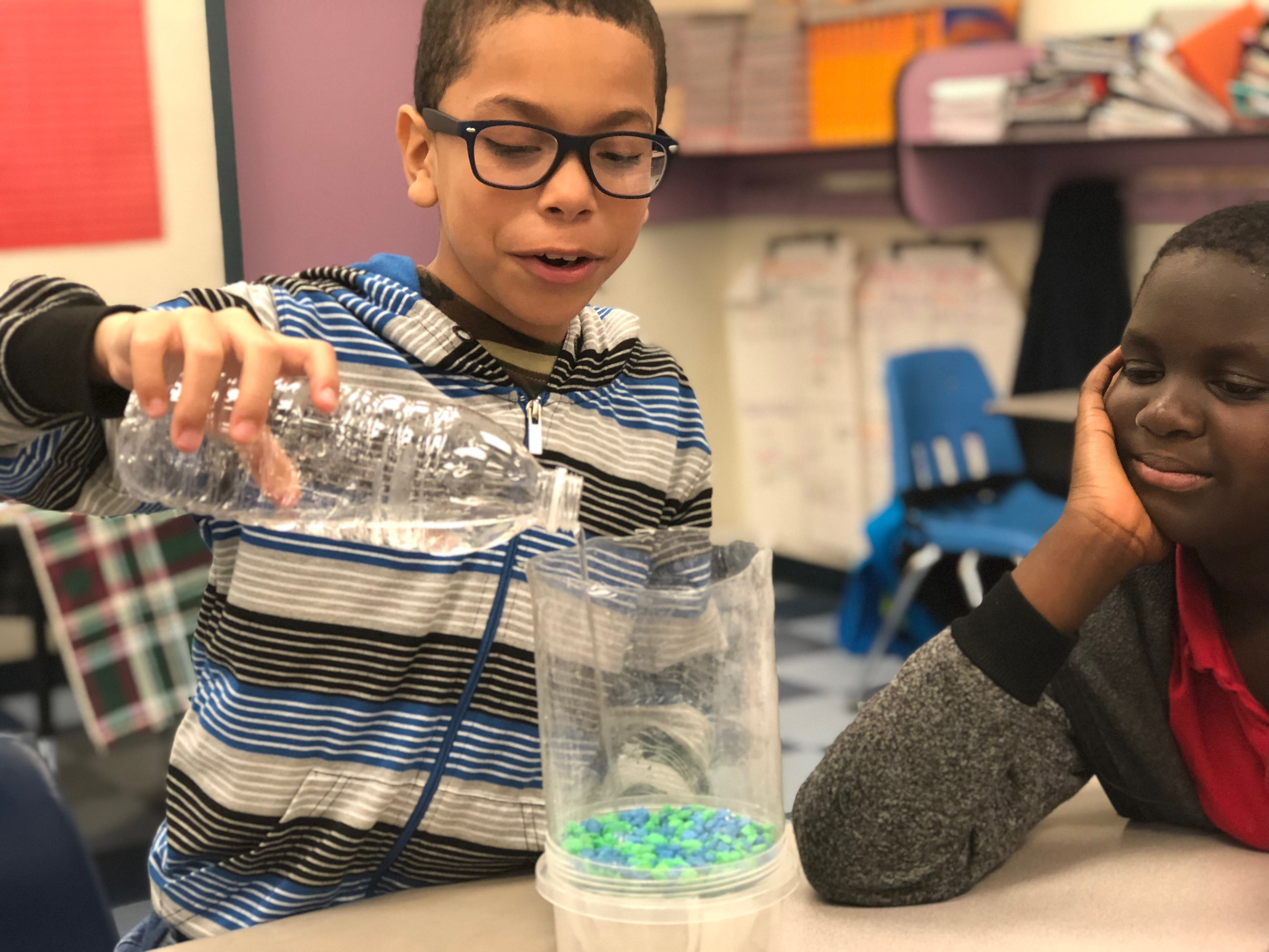 Student pouring water into his water filtration system