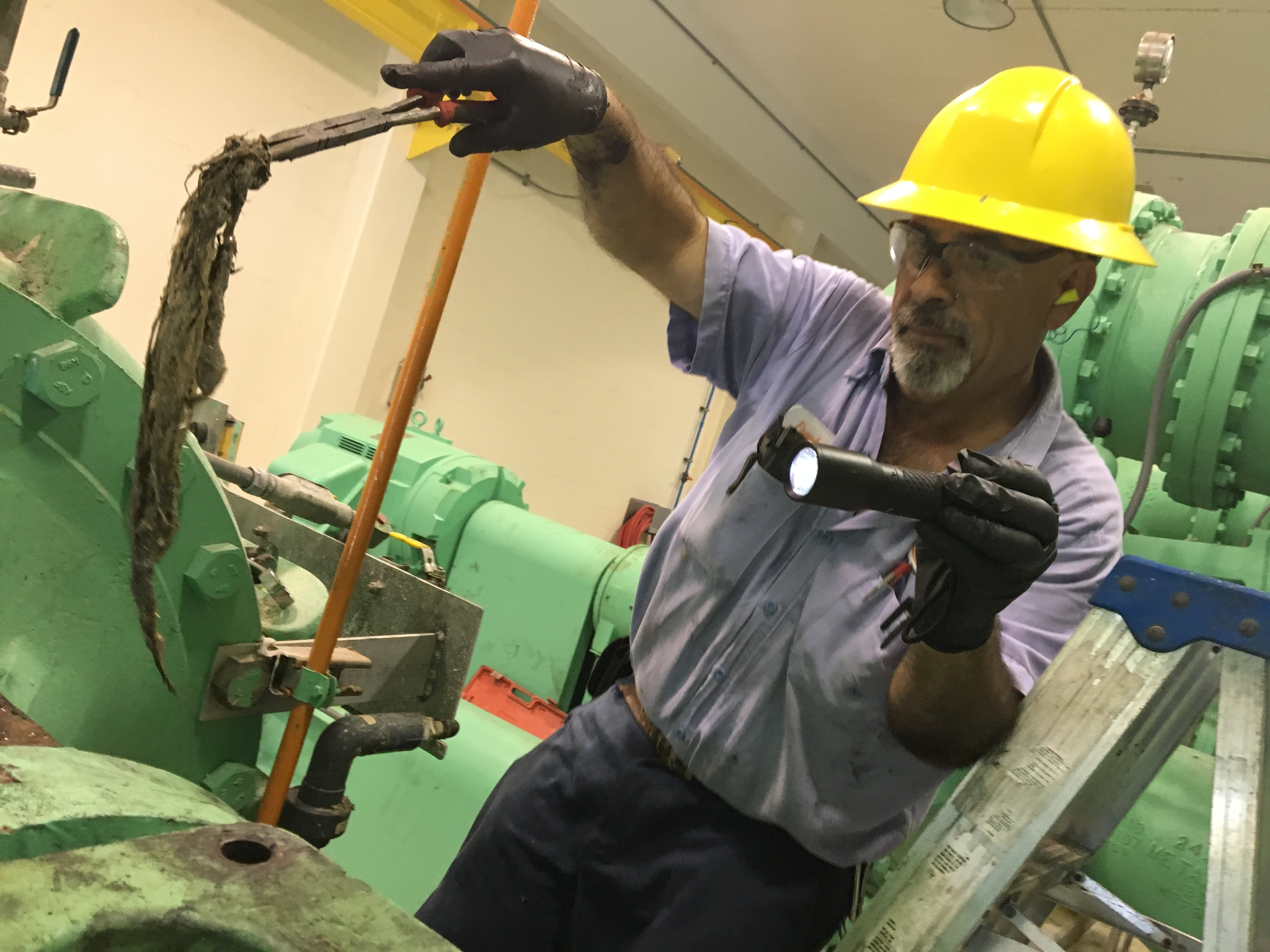 Employee pulling wipes clumped together out of sewer booster pump
