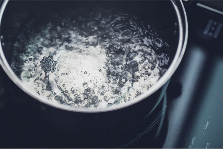 Water boiling in a pot on the stovetop.