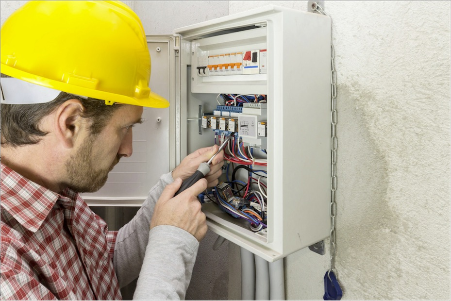 Licensed electrician in hard hat working on home's electrical panel.