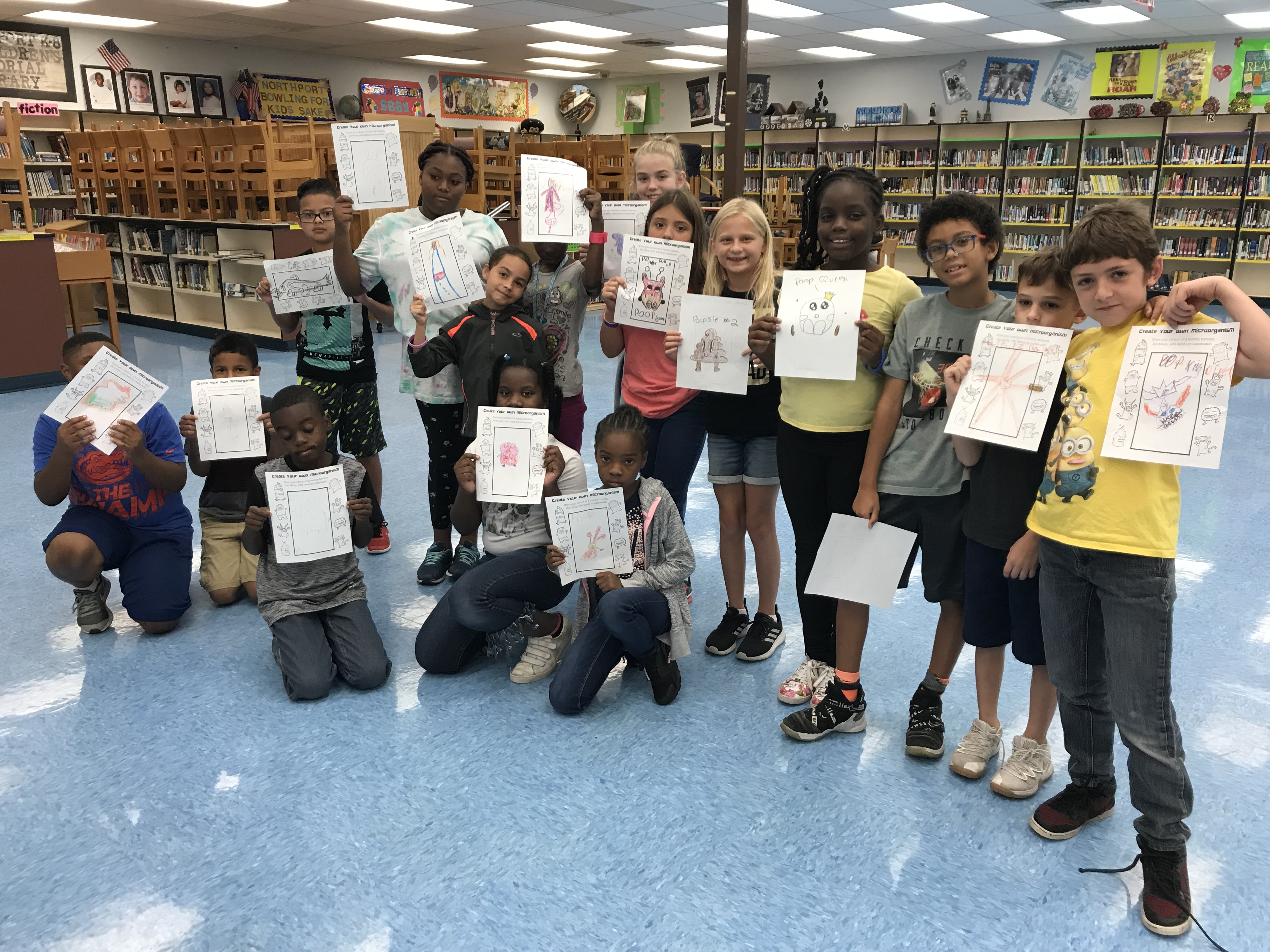 Group of kids show off their microorganism drawings