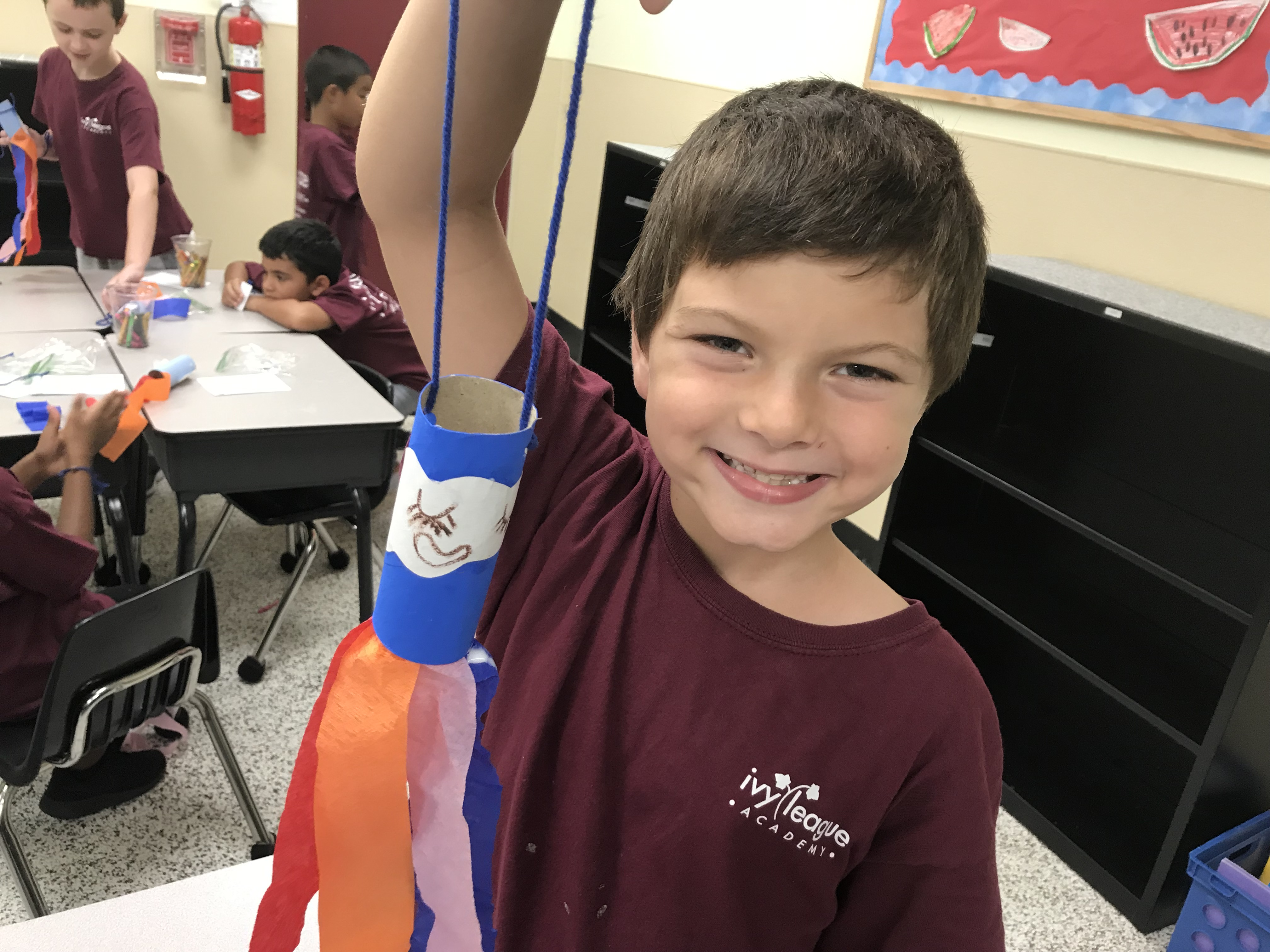 Young boy shows off his rainbow toilet paper roll craft