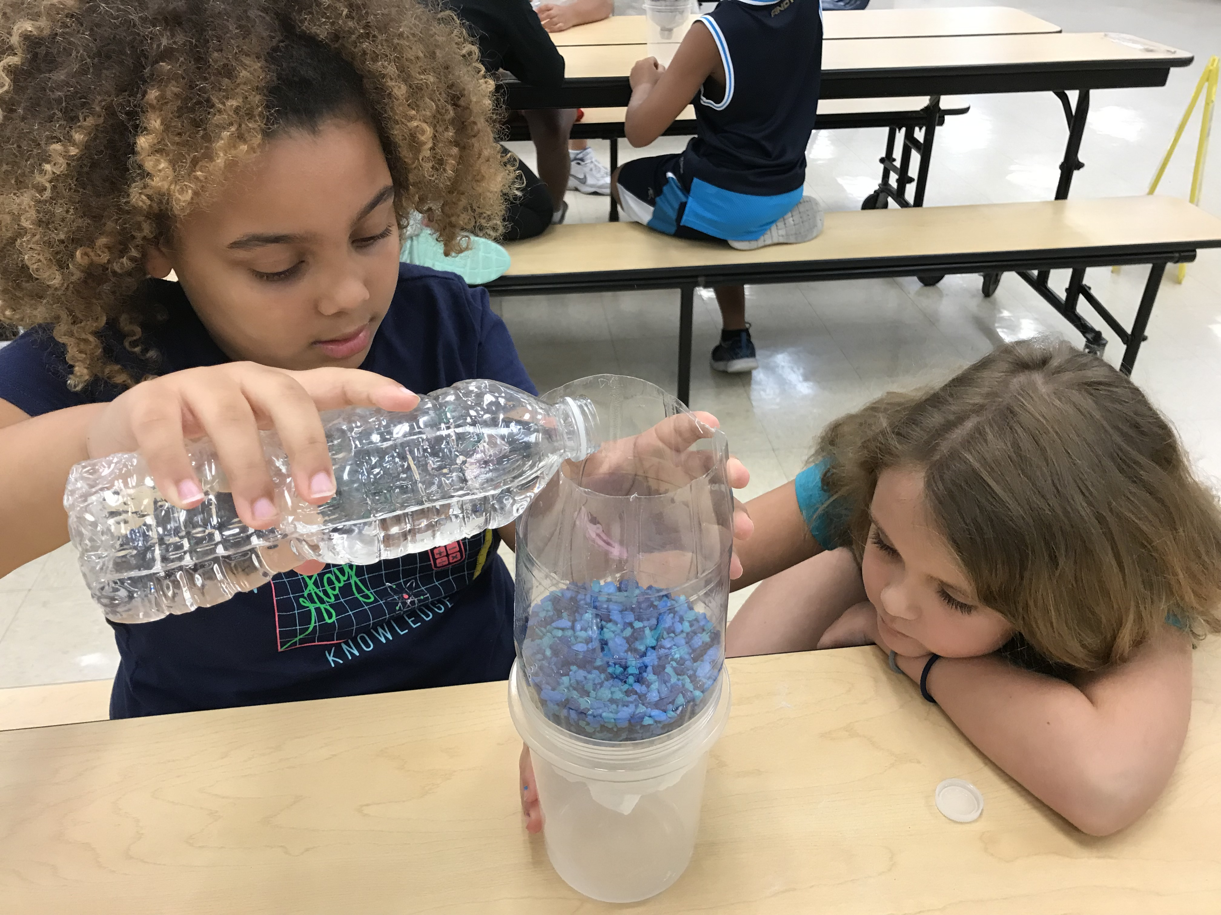 Girl pouring water into her water filter project as her partner watches