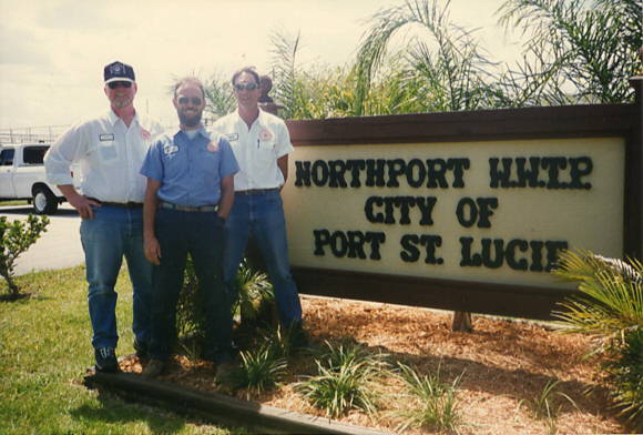 Group photo of 3 employees standing in front of Northport Wastewater Treatment Plant sign